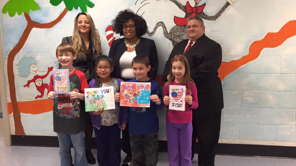 Assemblywoman Kimberly Jean-Pierre stands with elementary school students of the 11th Assembly District who made Valentine's cards for Veterans and Senior Citizens.