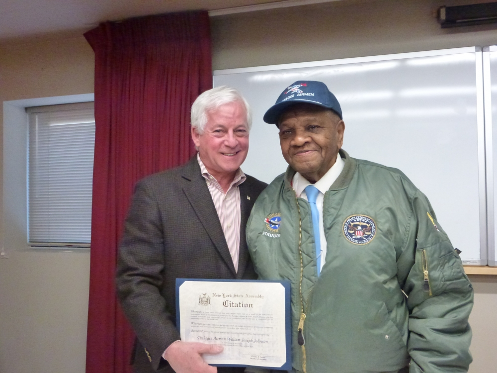 Assemblyman Charles Lavine (D-13) presents Glen Cove resident William Joseph Johnson with a citation recognizing his service during World War II as one of the Tuskegee Airmen. Mr. Johnson, who grew up in Glen Cove and returned following the war, recounted his story as a member of the legendary all-black unit that trained in Tuskegee, Alabama as pilots. He inspired a group of local community members on hand at the Glen Cove Library with tales of his life before and after the war.