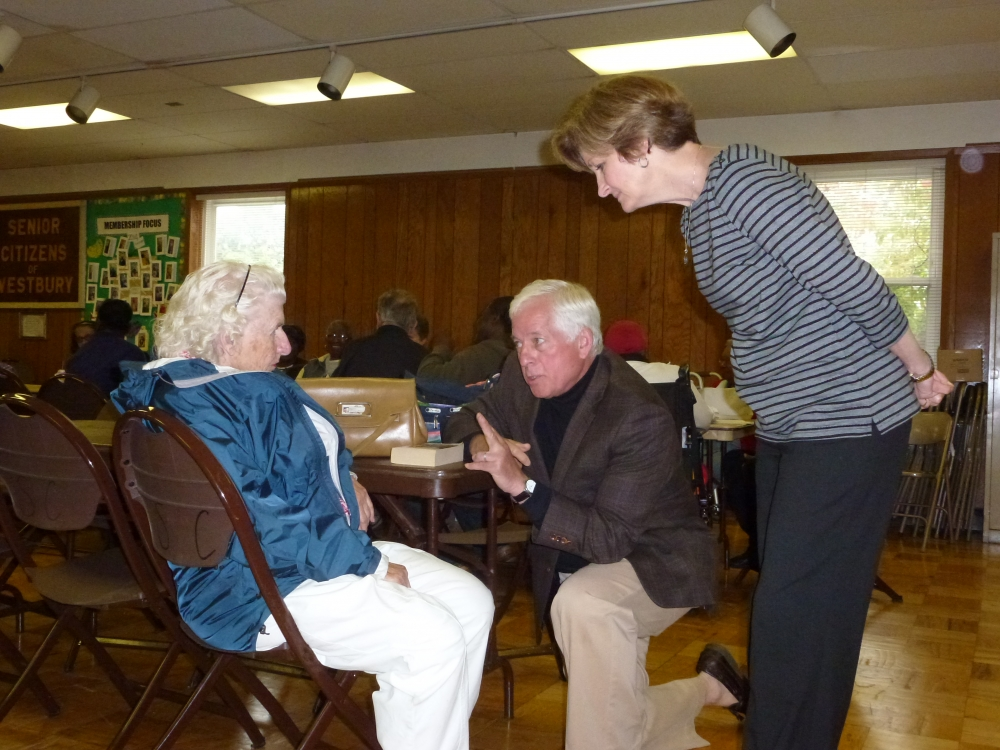 Assemblyman Charles Lavine (D-Glen Cove) makes a point to Muriel Tatem on a recent visit to the Senior Citizens of Westbury, Inc. while Maureen Droge, Executive Director, listens in. Assemblyman Lavin