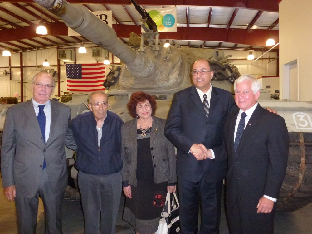 Assemblyman Charles Lavine (D-Glen Cove) right, greets Ido Aharoni, Consul General of Israel and his parents Ahuva and Emanuel Aharoni at an event at the Museum of American Armor at Old Bethpage Village Restoration during a dedication ceremony of an M48 tank (rear) used during the 1973 Yom Kippur War. The tank was built by the U.S. and transferred to Jordan in the 1960�s. In 1967 it was captured by the Israelis during the Arab-Israeli conflict and then deployed during the 1973 Yom Kippur conflict. The tank was purchased by a collector who brought it to the U.S. It was acquired by a philanthropist for display at the Museum in Old Bethpage as a reminder of the sacrifices made in the defense of democracy.