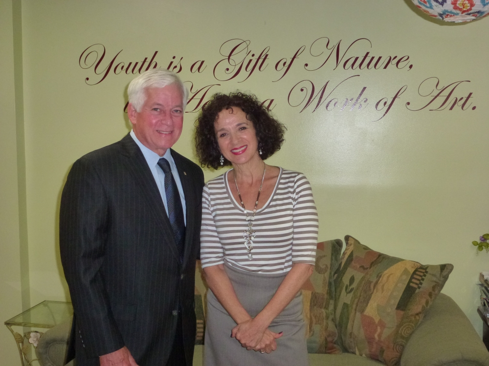 Assemblyman Charles Lavine (D-Glen Cove) and Lisa Craig, Program Director of the Glen Cove Adult Day Program, stand beneath a sign that states �Youth is a Gift of Nature, Aging is a Work of Art� during Assemblyman Lavine�s recent visit to the Glen Cove Senior Center to meet and greet the seniors who are benefitting from a $5,000 grant he secured for social and recreational activities as well as general day care.