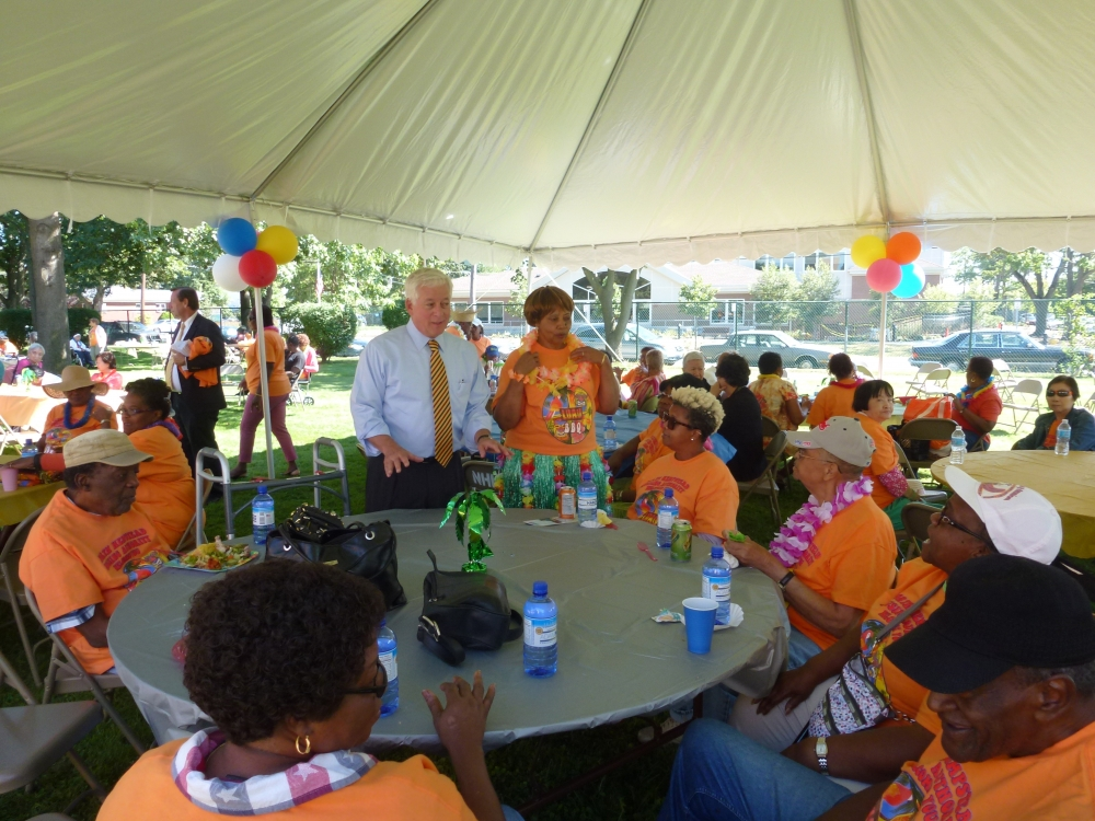 Assemblyman Charles Lavine (D-Glen Cove) is joined by Estelle Meyers as he talks with residents of Magnolia Gardens in New Cassel as well as other housing complex residents during the Town of North Hempstead Housing Authority�s annual barbecue. Hawaiian-inspired food and drinks, including a roast pig were on the menu as was music and entertainment.