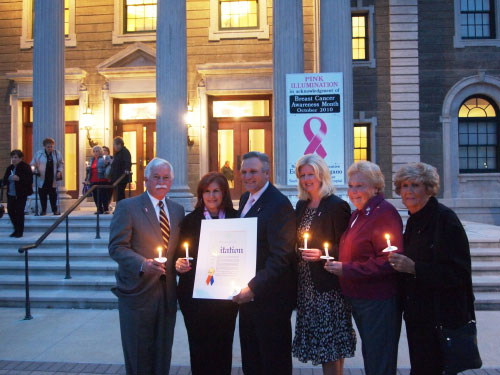To mark the designation of October as Breast Cancer Awareness Month, Assemblyman Charles D. Lavine joined other supporters at The Theodore Roosevelt Executive and Legislative Building in Mineola for the annual Glow of Hope ceremony. The candlelight event, a joint venture of Nassau County and 1 in 9/Hewlitt House, pays tribute to all breast cancer victims, survivors and their families. It concludes with the pink illumination of the building's dome. Pictured at Glow of Hope are Assemblyman Lavine; Geri Barish, cofounder and president of 1 in 9: The Long Island Breast Cancer Action Coalition and executive director of Hewlett House; Nassau County Executive Ed Mangano; Dr. Christine Hodyl, director of breast surgery at South Nassau Communities Hospital; Nassau County Legislator Rose Marie Walker; and Louise Levine, vice president and cofounder of 1 in 9: The Long Island Breast Cancer Action Coalition.