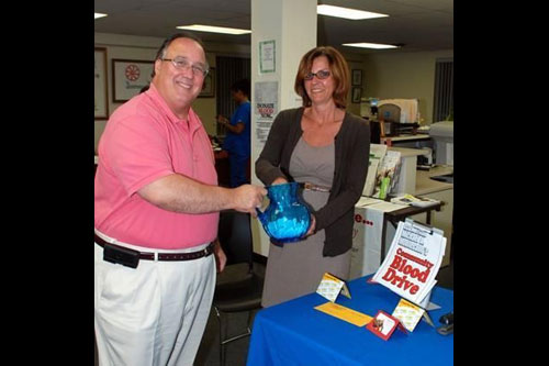 Assemblyman Michael Montesano and Clare Trollo, Hicksville resident and Gold Coast Public Library Adult Program Coordinator, raffle gifts to donors at the Assemblyman�s community blood drive on July 23.
