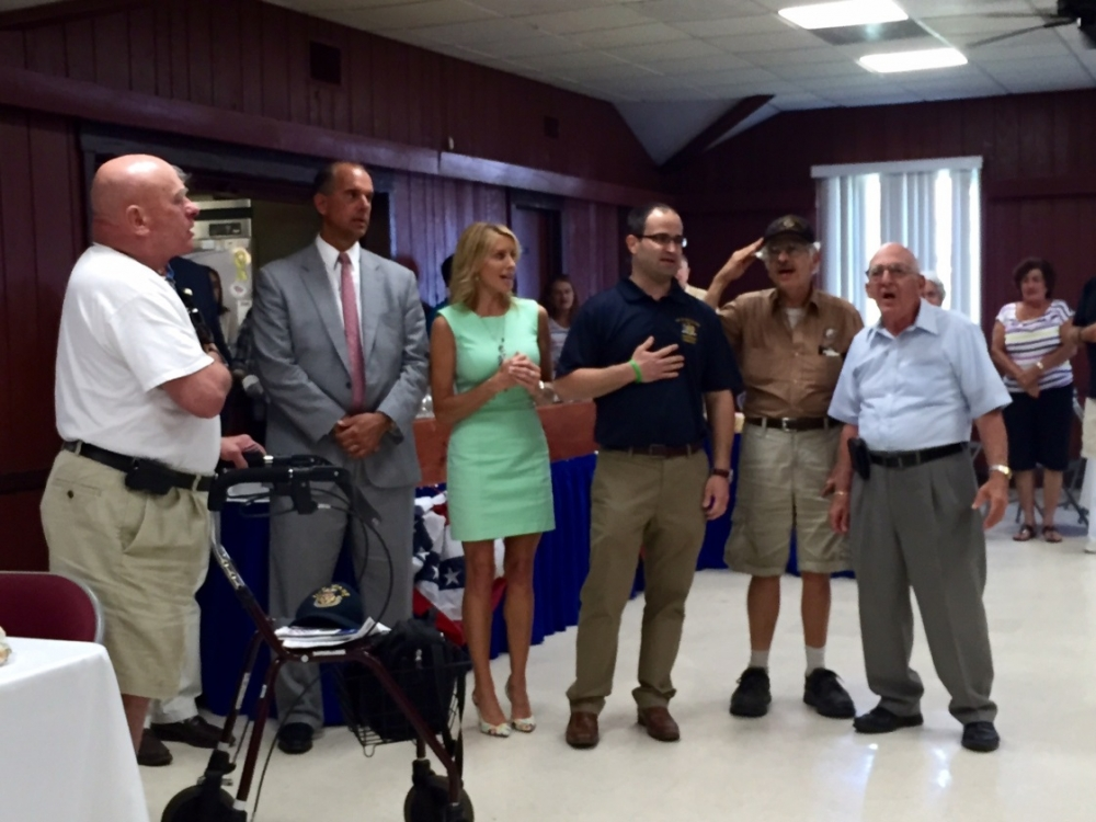 Assemblyman Ed Ra leads the crowd in the singing of God Bless America. He is joined by Hempstead Town Councilman Ed Ambrosino and Nassau County Legislator Laura Schaefer, along with local veterans, at the Heroes Night Out BBQ on August 13, 2015 at VFW Post 2718.
