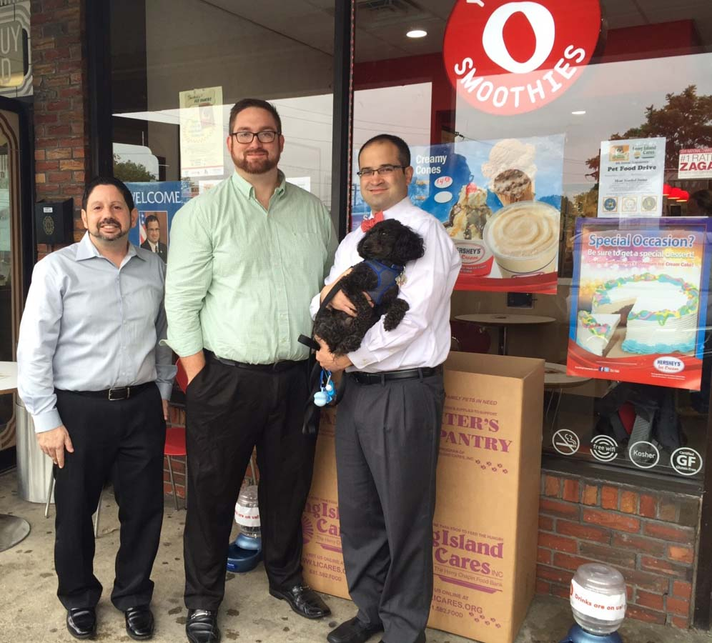 Assemblyman Ed Ra and his dog Carter, along with Chris Cianciulli, owner of Red Mango in Franklin Square, and Michael W. Haynes of Long Island Cares, Inc. help kickoff a local pet food drive to benefit Baxter's Pet Pantry operated by Long Island Cares Inc.