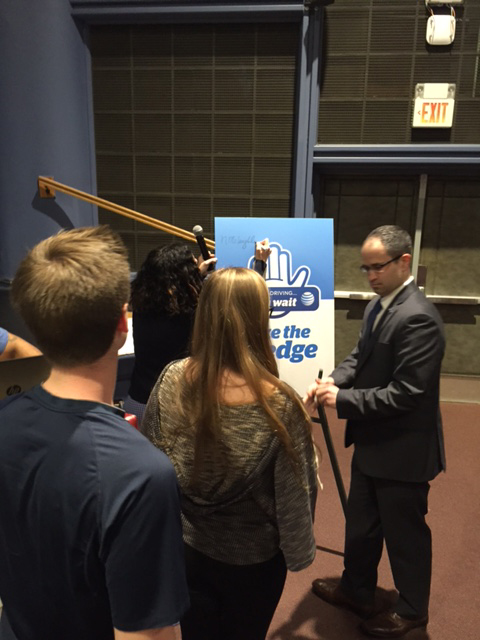 "Assemblyman Ed Ra assists the students of Garden City High School as they sign the AT&T ""It Can Wait"" pledge board. By adding their signature, the students are promising to keep their eyes on the road, not on their phone."