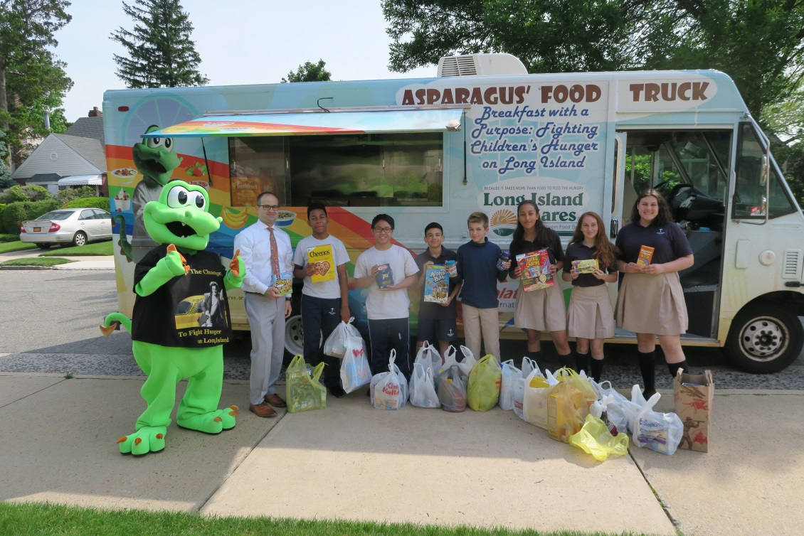 Asparagus the Dragon, mascot of Long Island Cares, picked up the 1,033 pounds of food from Assemblyman Ed Ra (R-Franklin Square) and students at Notre Dame School, New Hyde Park, on Friday, June 8.