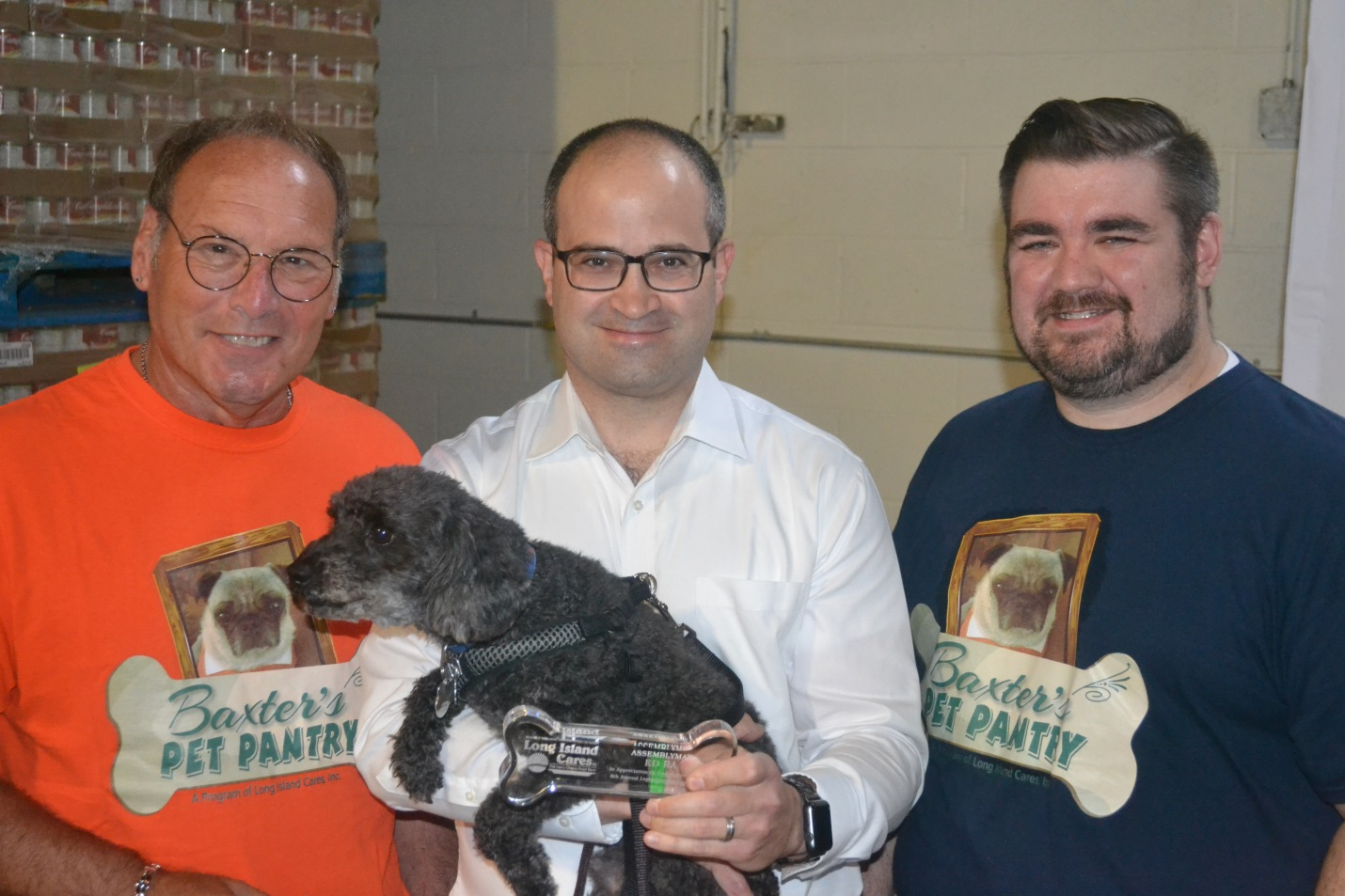 Assemblyman Ra (center) and his rescue dog, Carter, accept an award from Long Island Cares CEO, Paule T. Pachter (left) and Community Events and Food Drive Manager, Billy Gonyou (right) for their part