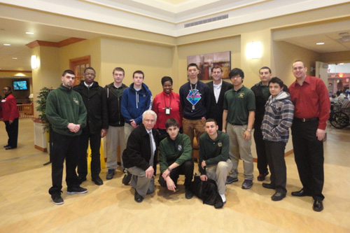 On Thursday, February 14, 2013, Assemblyman Braunstein and his staff, along with the students of Holy Cross High School, delivered donations from the 17th Annual Valentines for Vets gift drive to the New York State Veterans� Home at St. Albans, pictured here with Chief of Staff David Fischer, Deirdre Samuel, Coordinator of Volunteer Services, and Michael Genovese, Director of Service Learning, with his students from Holy Cross High School.