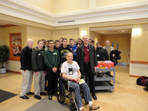 Assemblyman Braunstein's Chief of Staff, David Fischer accompanied by Holy Cross High School students and Director of Service Learning, Michael Genovese, celebrating Valentines for Vets with retired serviceman James Weir and Deirdre Samuel, Coordinator of Volunteer Services at the NYS Veterans Home at St. Albans.