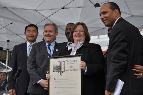 Assemblywoman Cathy Nolan, pictured with City Comptroller John Liu and City Councilmember Jimmy Van Bramer, presented Bishop Mitchell Taylor, President of East River Development Alliance, a proclamation for his dedication to ERDA.