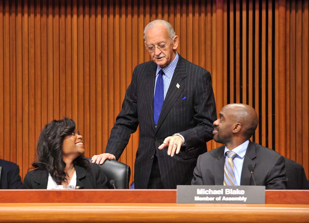 Assemblymembers Bichotte and Blake (right), talk with Denny Farrell, Chair of the Assembly Ways and Means Committee, prior to the start of a public hearing on housing. Bichotte is a member of the Housing Committee.