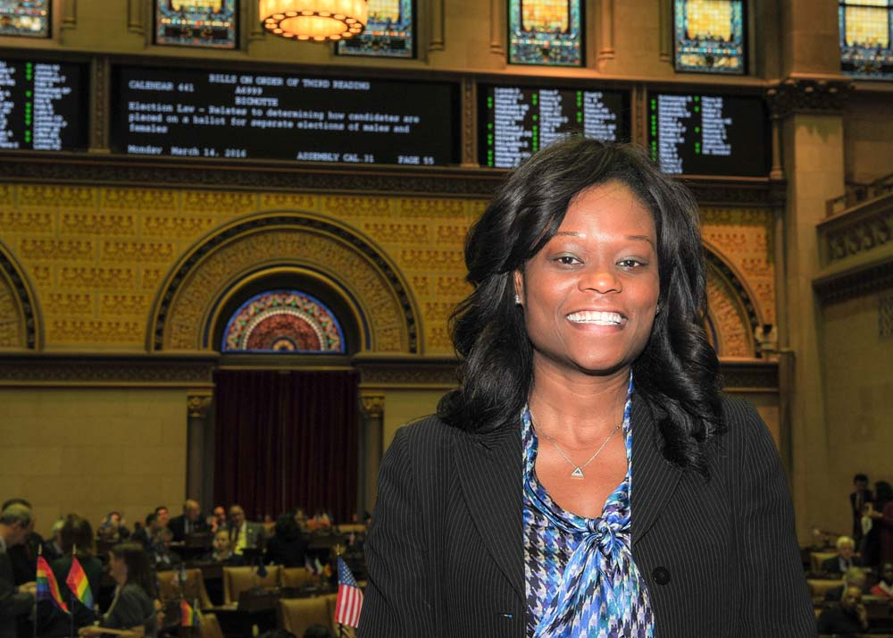 Assemblymember Bichotte is in Chamber with her bill, A-6999, shown in the background. The bill relates to determining how candidates are placed on a ballot for separate elections of males and females.