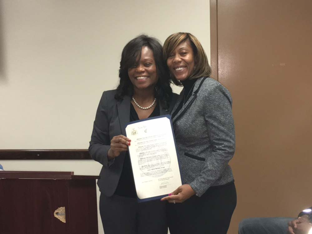 Assemblymember Bichotte at the 67th Precinct Community Council meeting presenting a citation to Police Officer Roxanne Joseph for being named Police Officer of the Year for exemplifying the best qualities of public service by empowering her community.
