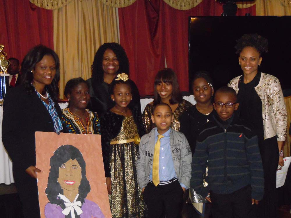 Assemblymember Bichotte with Joan Bakiriddan, Executive Director, Monique Waterman, Program Director, and young participants of East Flatbush Village at its Black History Month event.