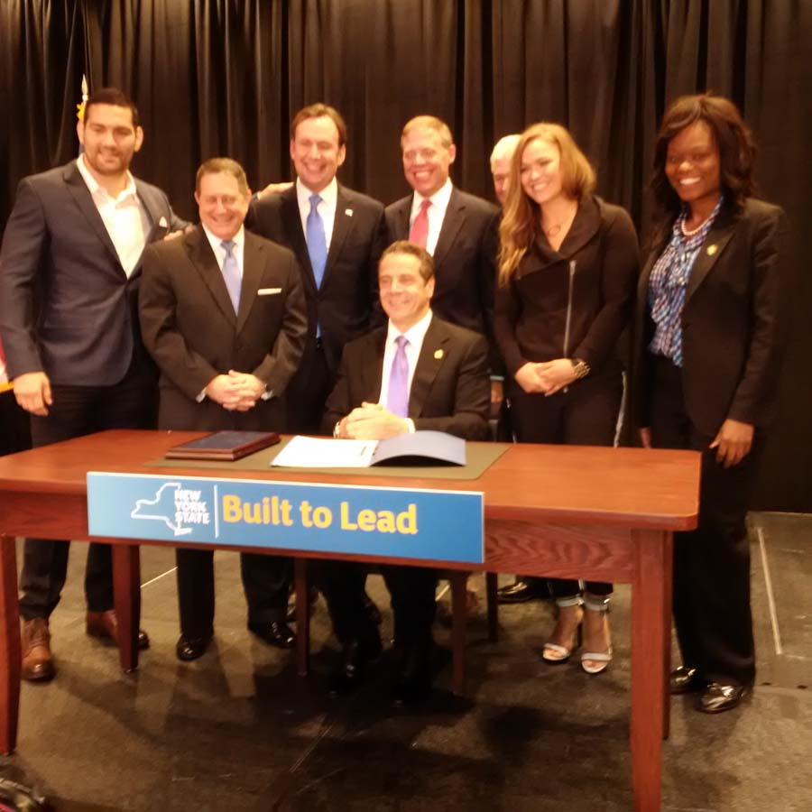 Assemblymember Bichotte, right, along with Governor Cuomo, Majority Leader Joe Morelle, and Ronda Rousey at the bill signing to make Mixed Martial Arts legal in New York State. The sport will likely generate significant revenue for the State.