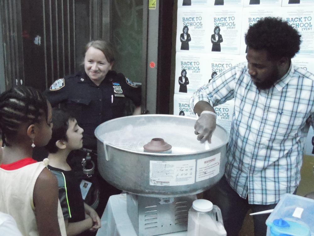 Director of Constituent Support Services, Francois Jeanty, serves cotton candy to residents of the 42nd Assembly, during the Back-to-School Supply Drive.<br />