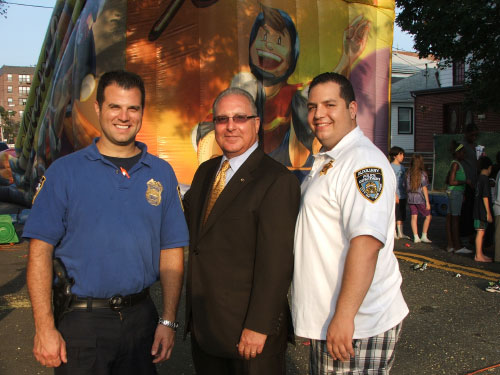 Assemblyman Cymbrowitz joined hundreds of community residents who attended the 61st Precinct�s �National Night Out.� The annual event is designed to bring the community together with police officers in an unstressful, upbeat setting. Pictured, with the Assemblyman, in front of one of the inflatable children�s rides (L-R) are Lt. Michael Doyle and Auxiliary Police Lieutenant Steven Matsas. Assemblyman Cymbrowitz joined his staff answering questions, providing informational pamphlets and offering free give-a-ways at a table they had set up.
