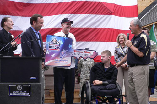 "Members of the Stephen Siller Tunnel to Towers Foundation present Brendan with a ceremonial key to his new ""smart home."" For more information on the Foundation, visit their website."