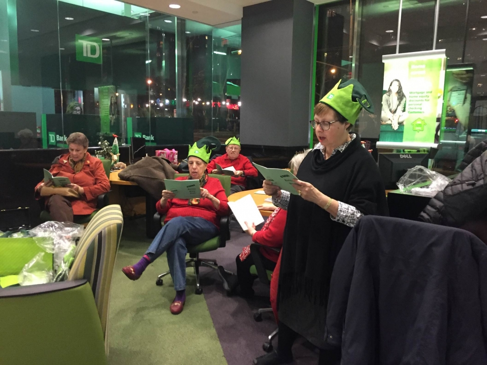 December 10, 2015--- TD Bank, Upper East Side---East Sixties Neighborhood Association�s Co-Presidents Judy and Barry Schneider host a holiday sing for the residents of the East Sixties.