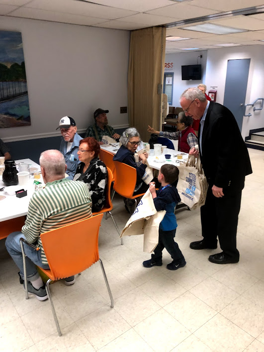 Assemblyman Jeffrey Dinowitz is helped by his grandson as they distribute reusable canvas bags from Citizens Committee of New York City to seniors at Riverdale Senior Services.