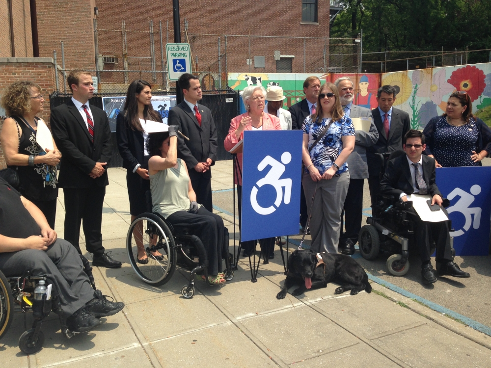 Sandy and Senator David Carlucci were joined by advocates for people with disabilities to urge Governor Cuomo to sign their legislation (A.9934/S.6846) which modernized the Universal Symbol of Access to be implemented throughout New York State. Governor Cuomo later signed this legislation into law which took effect in November 2014.