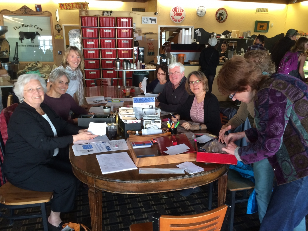 Sandy sitting down at the Black Cow with constituents who were writing postcards to their federal and state representatives.