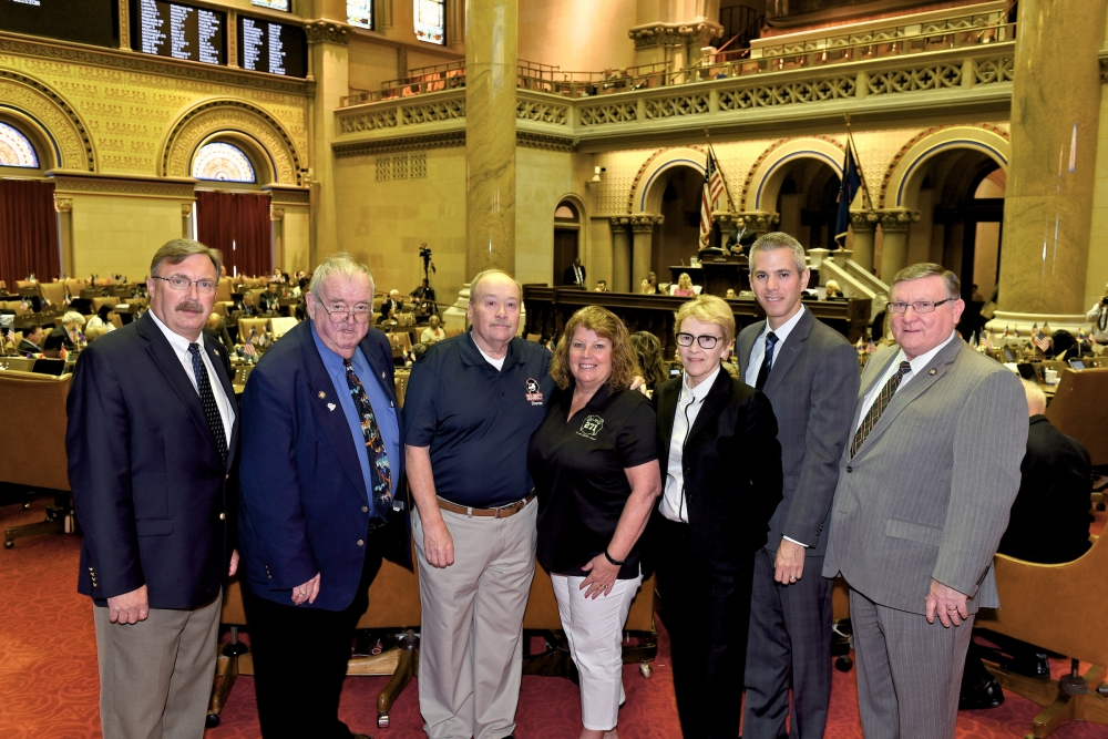 Assemblyman Brian Miller with volunteer firefighter Brian McQueen, his wife and other legislators as legislation passes to provide enhanced disability benefits to volunteer firefighters who develop certain forms of cancer.<br />