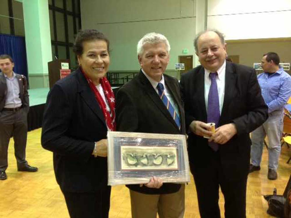 Assemblymember Cahill holds a gift from the Turkish Cultural Center Albany as he stands alongside attendees Feray Girgin Lues (left) and Oguz Alpoge (right) at Turkish Cultural Night at SUNY New Paltz