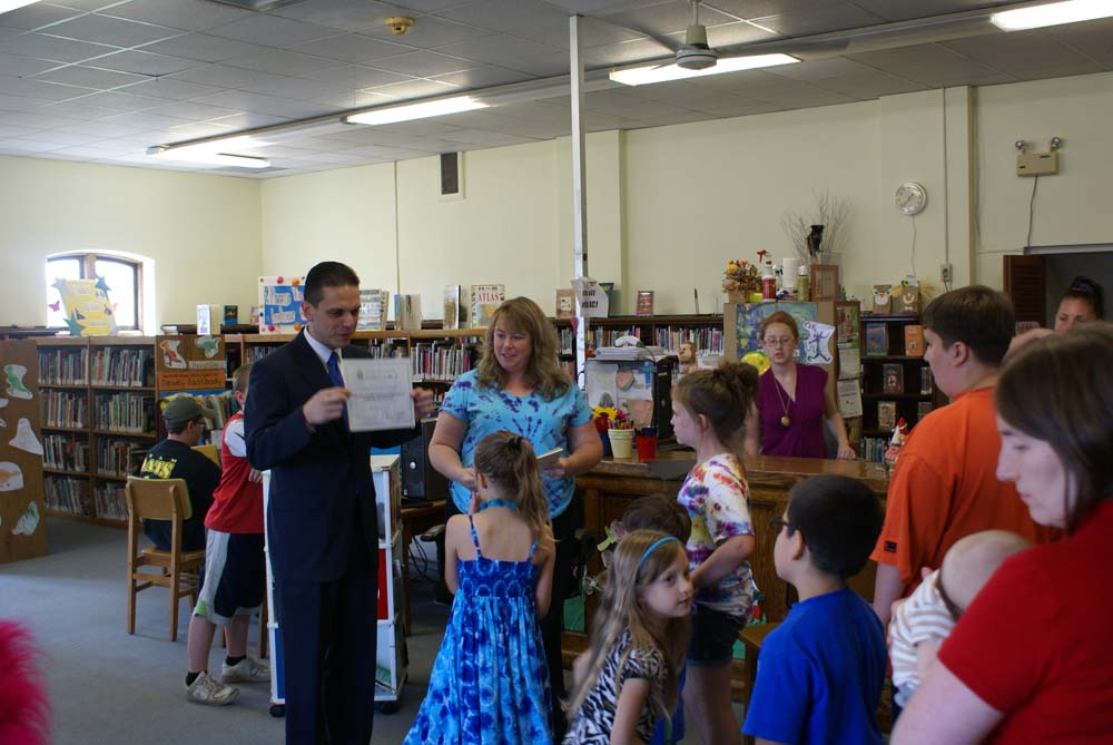 Assemblyman Santabarbara awards certificates to children who completed the Amsterdam Free Library�s Summer Reading Program.