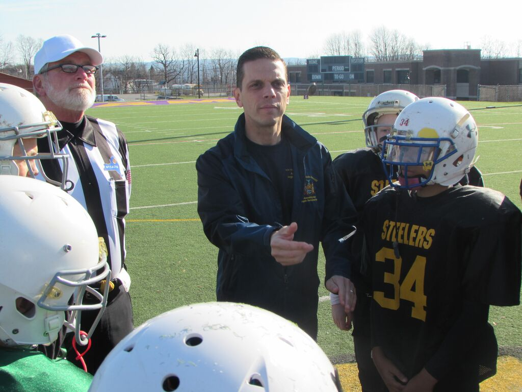 Assemblyman Angelo Santabarbara performs the coin toss before the Amsterdam Little Giants� Super Bowl after presenting the youth football league with new helmets and a $2,500 check for the purpose of buying additional safety equipment. 11/15/2015