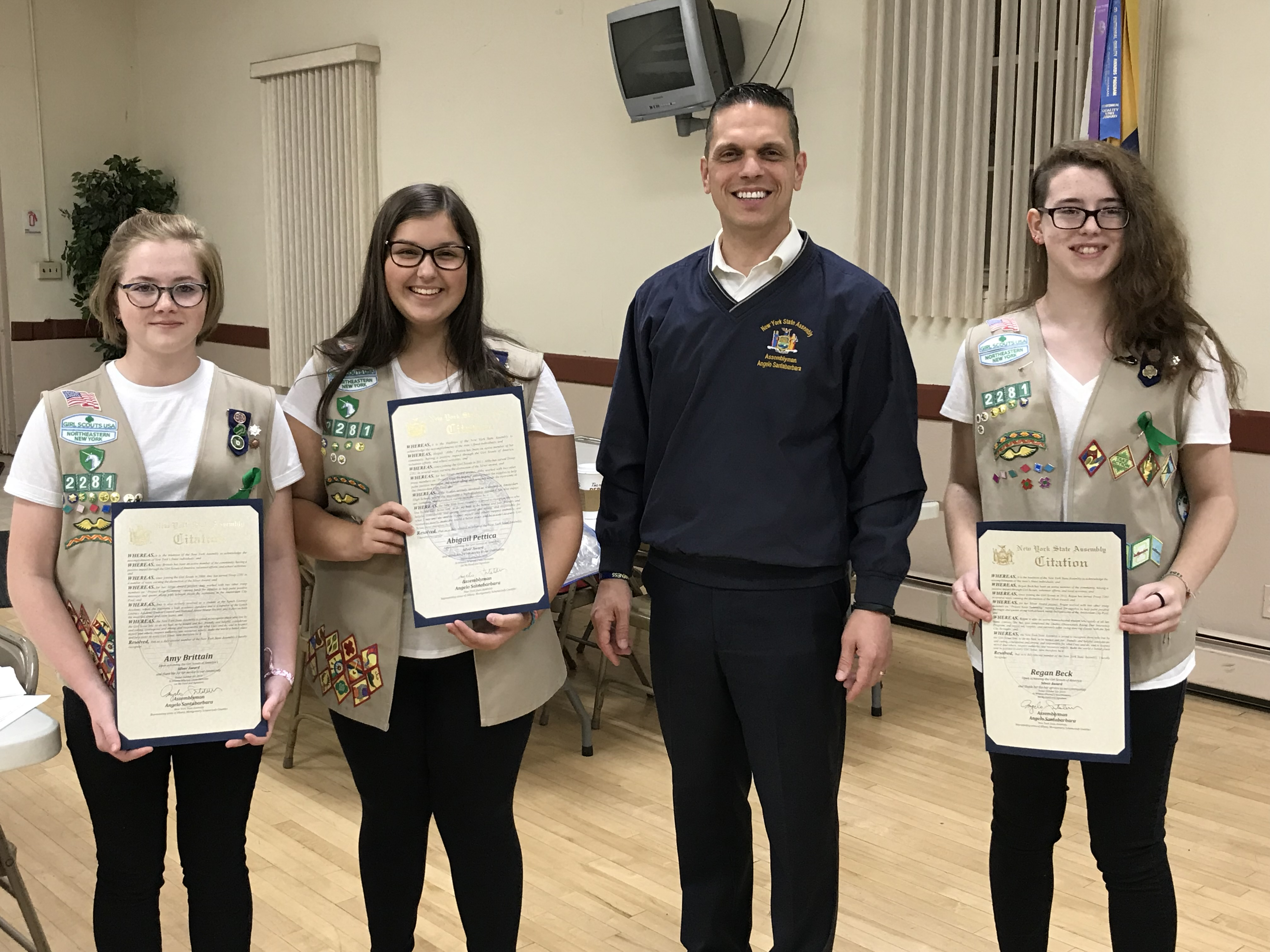 Assemblyman Angelo Santabarbara presents Amy Brittain, Abigail Pettica, and Regan Beck from Girl Scout Troop 2281 in Amsterdam with citations from the New York State Assembly recognizing their Silver