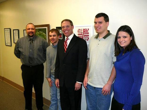 Assemblyman Will Barclay (R,C,I�Pulaski) worked with ARISE to have artwork, which was published in UNIQUE, an Art and Literary Magazine that shares the artistic visions and voices of individuals with disabilities throughout the region, on display outside his office on the second floor of the Oswego County building earlier this year. UNIQUE publishes poems, paintings, drawings, photographs, sculptures, computer-based art, and mixed-media annually. Pictured here, from left, Chris Scoville, Medicaid Service Coordinator; Derek Grindle, artist; Assemblyman Will Barclay; Jeremy Kelley, artist; and Jineane Hanson, Medicaid Service Coordinator.