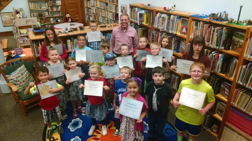 "Almost 70 children throughout the area participated in Assemblyman Will Barclay's summer reading program. The recognition party was held Saturday, September 26 at the Fulton Public Library. Barclay read two stories and handed out certificates to those in attendance. Snacks and crafts also were provided. Pictured in front is Aliana London Vazquez (Fulton). In second row are Henry Jerred (Fulton), Grace Carguello (Pulaski), Evan Rood (Pulaski), Roland ""Joey"" Stewart (Mexico), and Carter Cole (Baldwinsville). In third row are Mikayla and Madeleine Towner (Mexico), Eli Prior (Fulton), Logan Spoon (Fulton) and Andie Rose (Oswego). In fourth row are Mary Jerred (Fulton), Zach DeMott (Oswego), Miles Bandla (Oswego), Jesse Marthia (Mexico), Mason Freebern (Fulton) and Jordan Meyers (Fulton).  In back row is Alexander Marthia (Mexico) and Assemblyman Barclay."