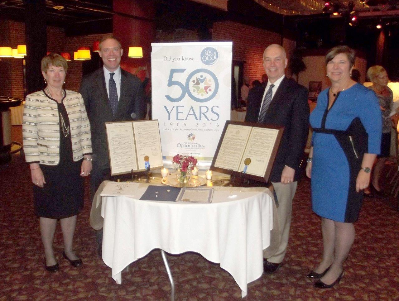 Assemblyman Will Barclay (R,C,I--Pulaski) and Assemblyman Bob Oaks (R,C�Macedon) recently congratulated Oswego County Opportunities on celebrating its 50th year anniversary at the organization�s annual meeting.  From left are President of the Board of Directors at OCO Connie Cosemento, Assemblyman Barclay, Assemblyman Oaks, and OCO Executive Director Diane Cooper-Currier.