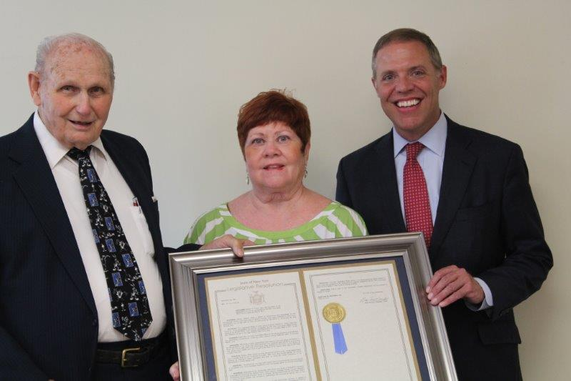Assemblyman Will Barclay (R,C,I-Pulaski), at right, presents an Assembly Resolution to long-time Fulton volunteer, Mr. Bob Green. Pictured with Barclay are Mr. Green and his wife, Sandy. Mr. Green was
