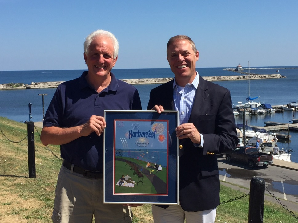 Oswego Harborfest's Executive Director Peter Myles presents Assemblyman Will Barclay (R,C,I,Ref-Pulaski) with the 2018 event poster.