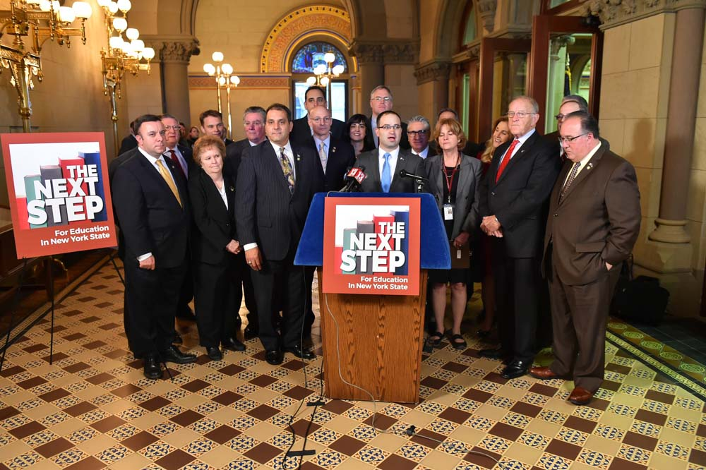 Assemblyman Christopher S. Friend (R,C,I-Big Flats), along with his Assembly Minority colleagues, looks on as Assemblyman Ed Ra begins recent press conference in Albany to announce their new education reform initiative, The Next Step.