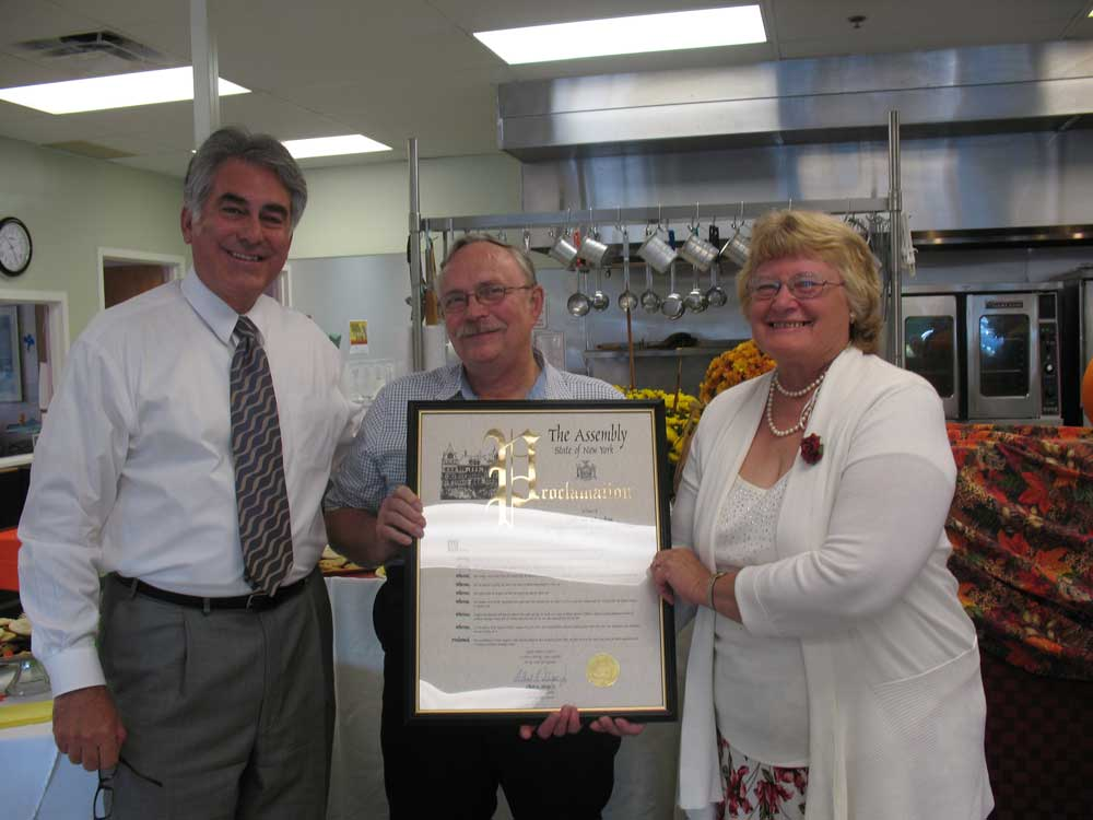 Assemblyman Stirpe presenting Linda and Robert Jackson a proclamation for their 40 years of volunteer service at North Area Meals on Wheels- North Syracuse.