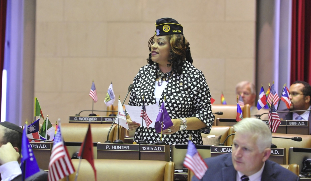 Assemblymember Hunter stands to introduce a group of women veterans from across the state in the assembly chamber.