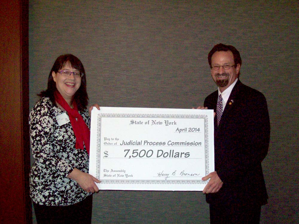 Assemblymember Bronson presents a check to Sue Porter from the Judicial Process Commission for $7,000. The money was secured by Bronson through the Edward Byrne Memorial Justice Assistance Grant Progr