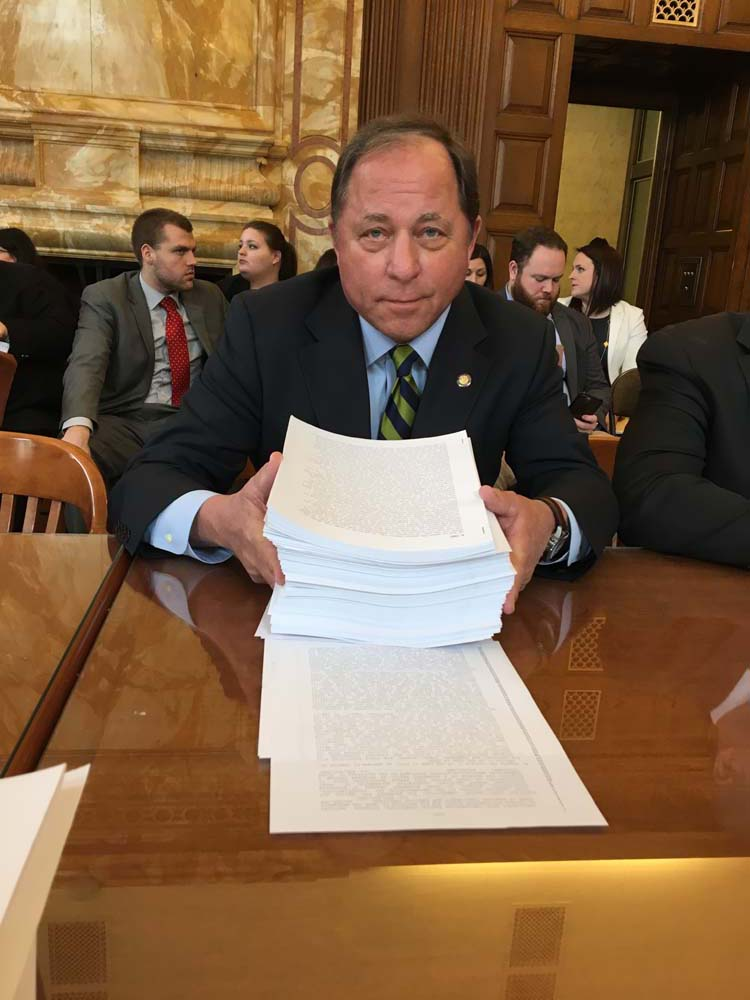Assemblyman Steve Hawley (R,C,I-Batavia) poses with nearly 2,000 pages of 'budget extender' legislation that was passed by the Legislature Monday following a stalemate in negotiations.<br />