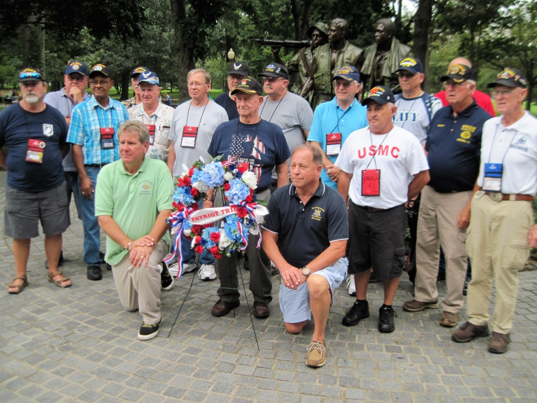 Assemblyman Steve Hawley [right of wreath] poses for a photo with Assemblyman Michael DenDekker [left of wreath] and veterans in front of the Vietnam War Memorial during 2018's Patriot Trip to Wa